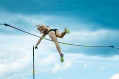 竞争在撑竿跳高的一个女运动员 免版税库存照片