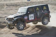 竞争在沙漠集会的越野卡车 图库摄影