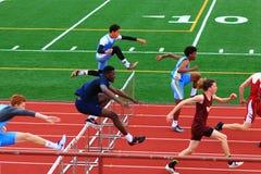 竞争在障碍的男孩在轨道竞争 免版税库存照片