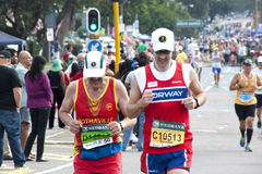 竞争在Marathon同志公路赛的幼小和老赛跑者 库存照片
