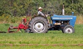 竞争推进耕犁犁拖拉机 免版税库存照片