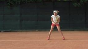 竞争精神,集中和集中于比赛和球拍命中球的坚定的雄心勃勃的儿童女孩网球员 股票录像