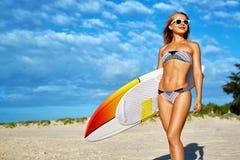 竞争跳水池炫耀游泳水 冲浪 有冲浪板的妇女暑假假期 免版税库存图片