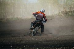 竟赛者在多灰尘的轨道的摩托车乘驾 库存照片