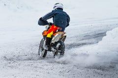 竟赛者在积雪的路的摩托车乘驾 免版税库存图片