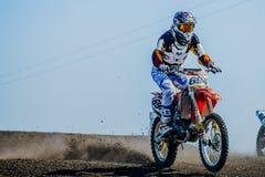竟赛者在轨道的摩托车骑士骑马在土下轮子  库存图片