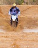 竟赛者通过泥乘坐摩托车 库存照片