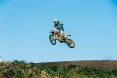 竟赛者从山的摩托车跃迁在蓝天背景 免版税图库摄影