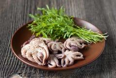 章鱼和蔬菜沙拉在一块板材在桌上 免版税库存图片