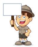 童子军或拿着一个空白的标志的探险家男孩 图库摄影
