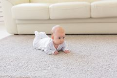 童年、婴儿时期和人概念-在家爬行在地板上的小男婴或女孩 库存图片