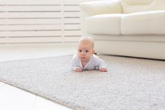 童年、婴儿时期和人概念-在家爬行在地板上的小男婴或女孩 免版税图库摄影