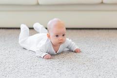 童年、婴儿时期和人概念-在家爬行在地板上的小男婴或女孩 免版税库存照片