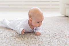 童年、婴儿时期和人概念-在家爬行在地板上的小男婴或女孩 免版税库存图片