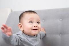 童年、婴儿时期和人概念-愉快的矮小的女婴在家坐沙发 库存图片