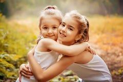 童年、家庭、友谊和人概念-拥抱两个愉快的孩子的姐妹户外 免版税图库摄影