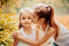 童年、家庭、友谊和人概念-拥抱两个愉快的孩子的姐妹户外 免版税库存图片