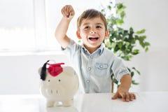 童年、金钱、投资和愉快的人概念-有存钱罐和金钱的微笑的小男孩在家 库存照片