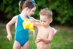 童年与水池的夏天比赛 白种人兄弟和姐妹戏剧用飞溅塑料玩具喷壶倾吐的水, 免版税库存图片