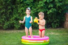童年与水池的夏天比赛 白种人兄弟和姐妹戏剧用飞溅塑料玩具喷壶倾吐的水, 库存图片