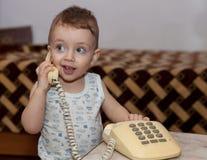童年和玩具概念-使用与电话的好奇孩子 免版税库存照片