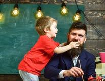 童年概念 父亲绘画,当儿子分散他时 握他的在爸爸s嘴的小孩手 免版税库存照片