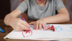 童年,学龄前年龄的孩子的发展 一个逗人喜爱,微笑的孩子在家坐在桌上并且画  股票视频