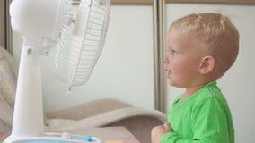 童年,家庭概念-有大冷却风扇的逗人喜爱的小男孩 影视素材