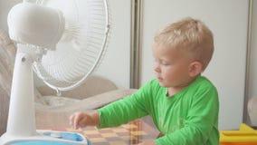 童年,家庭概念-有大冷却风扇的逗人喜爱的小男孩 股票录像