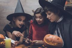 童话妖怪服装的三个孩子为万圣夜被删去从纸的棒 免版税库存照片