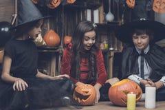 童话字符服装的孩子为万圣夜考虑一盏南瓜灯 库存图片