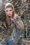 童话字符的美丽的柔和的甜女孩在走通过有蝴蝶的森林的木矮子的角色在她 免版税库存图片
