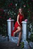 童话 坐在一个神秘的庭院里的红色礼服的美丽的公主 免版税库存照片