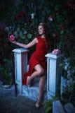 童话 坐在一个神秘的庭院里的红色礼服的美丽的公主 免版税库存图片