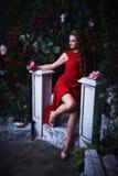 童话 坐在一个神秘的庭院里的红色礼服的美丽的公主 免版税图库摄影