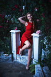 童话 坐在一个神秘的庭院里的红色礼服的美丽的公主 库存照片