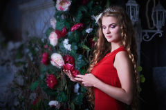 童话 坐在一个神秘的庭院里的红色礼服的美丽的公主 库存图片