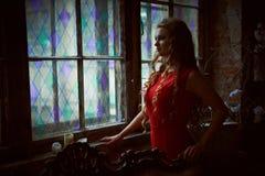 童话 坐在一个神秘的庭院里的红色礼服的美丽的公主 图库摄影