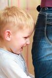 童年。不快乐的恼怒的男孩有孩子儿子和的母亲冲突。 图库摄影