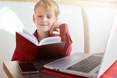 童年和休闲 坐在开放笔记本前面的严肃的小男孩画象读与巨大兴趣的一本书 免版税库存图片