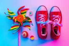 童年-运动鞋和玩具轮转焰火和橡胶球 库存照片