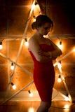 端庄的妇女剪影摆在反对大发光的礼服的 库存图片
