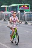 端庄的妇女在背景,北京,中国骑有公共汽车的一辆公开份额自行车 免版税库存照片