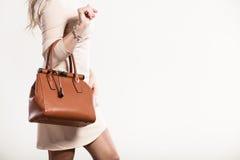 端庄的妇女拿着棕色提包 库存图片