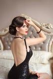 端庄的妇女美好的后面摆在mo的黑性感的礼服的 免版税库存图片