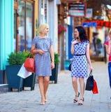 端庄的妇女走的五颜六色的城市街道 免版税库存图片