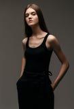 年轻端庄的妇女高档时尚画象黑裤子鞋子的 库存照片