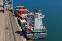 端起有集装箱船的船坞和运输货柜的各种各样的品牌和颜色在一个举行的平台堆积的 库存照片