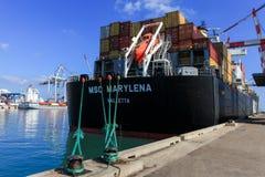 端起有集装箱船的船坞和运输货柜的各种各样的品牌和颜色在一个举行的平台堆积的 库存图片