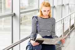 终端镶边的女衬衫的旅游白肤金发的妇女坐在驻地或和看地图 库存照片